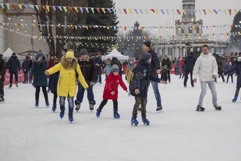 Kyiv Ukraina - 01 01 2018: lyckligt folk som åker skridskor på isbanan på vinterferierna royaltyfri fotografi