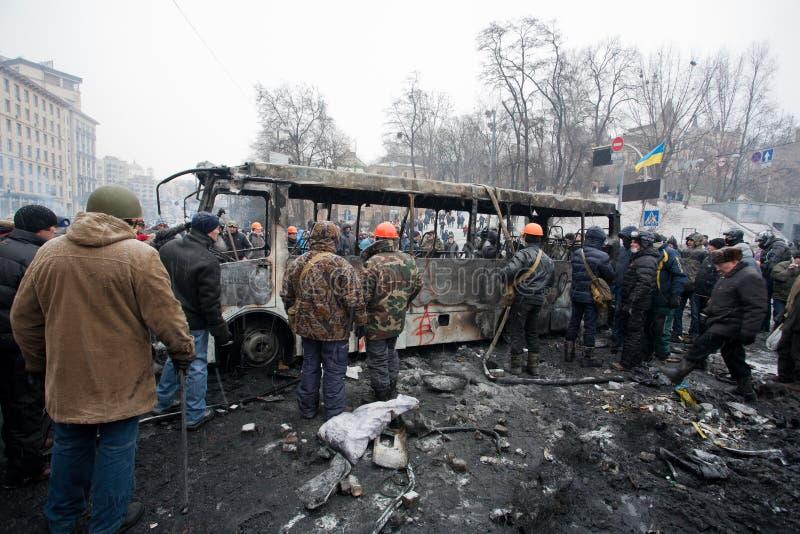 KYIV UKRAINA: Många män i likformig och hjälmar vulten bränd buss på den upptagande gatan under anti--regering protesterar royaltyfri foto