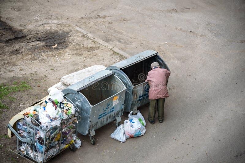 KYIV UKRAINA MARS 31, 2019: En hemlös man som söker efter mat i en avskrädedumpster stads- armod royaltyfria foton