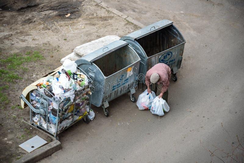 KYIV UKRAINA MARS 31, 2019: En hemlös man som söker efter mat i en avskrädedumpster stads- armod royaltyfria bilder