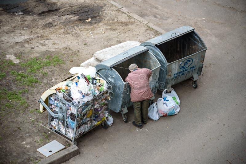 KYIV UKRAINA MARS 31, 2019: En hemlös man som söker efter mat i en avskrädedumpster stads- armod royaltyfri foto