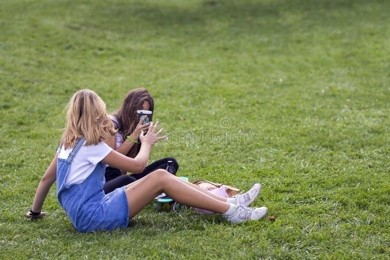 Kyiv Ukraina - November 14, 2017: Två unga flickor som sitter på gr arkivfoton