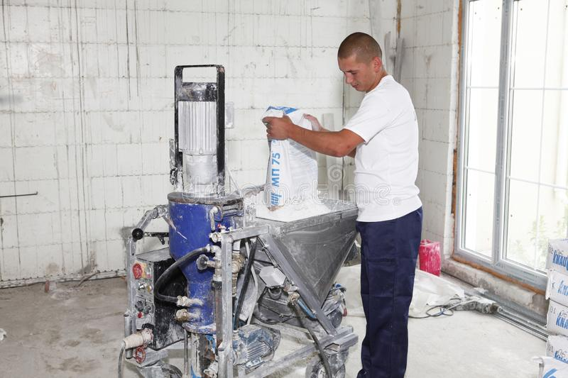 Contractor making plaster concrete with plastering machine for house plastering walls. Electric Spray Plaster Machine. Automatic royalty free stock image