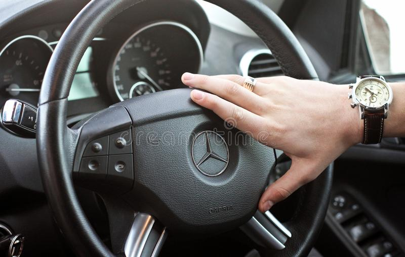 Kyiv, Ukraine, April 4, 2015: A man holds the steering wheel of Mercedes royalty free stock image