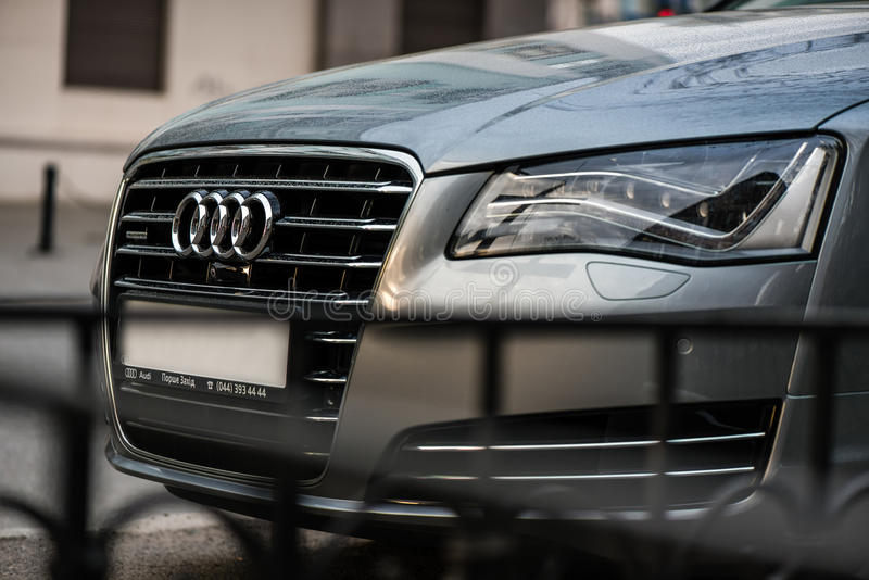 Kyiv, Ukraine - April 10th, 2016: The emblem on the front grille of a luxury Audi sedan on city street. The emblem on the front grille of a luxury Audi sedan on stock photography