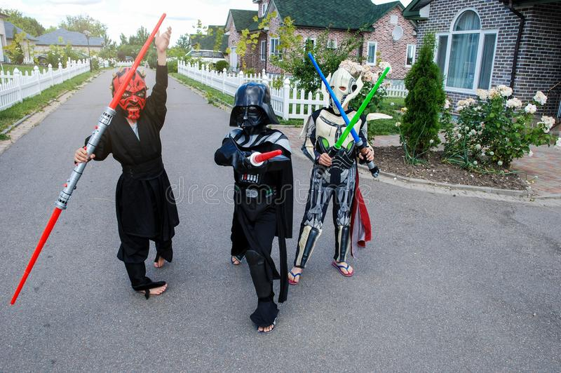 Children disguised in Star Wars costumes: Dart Maul, Darth Vader with swords. Darth Vader. Kyiv/Ukraine - August 15, 2018: Children disguised in Star Wars royalty free stock images
