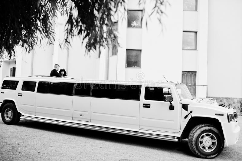 Kyiv, Ukraine - August 31: Elegance white wedding limousine Hummer H2 with newlyweds on car sunroof at wedding day. Black and stock image