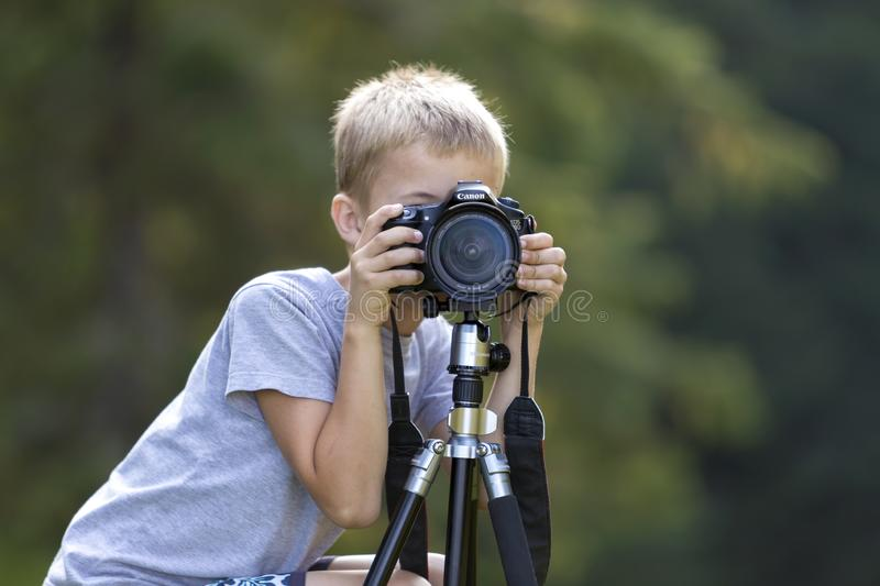KYIV, UKRAINE - August 25, 2018: Young cute blond child boy taking picture with tripod camera on blurred green copy space royalty free stock photo