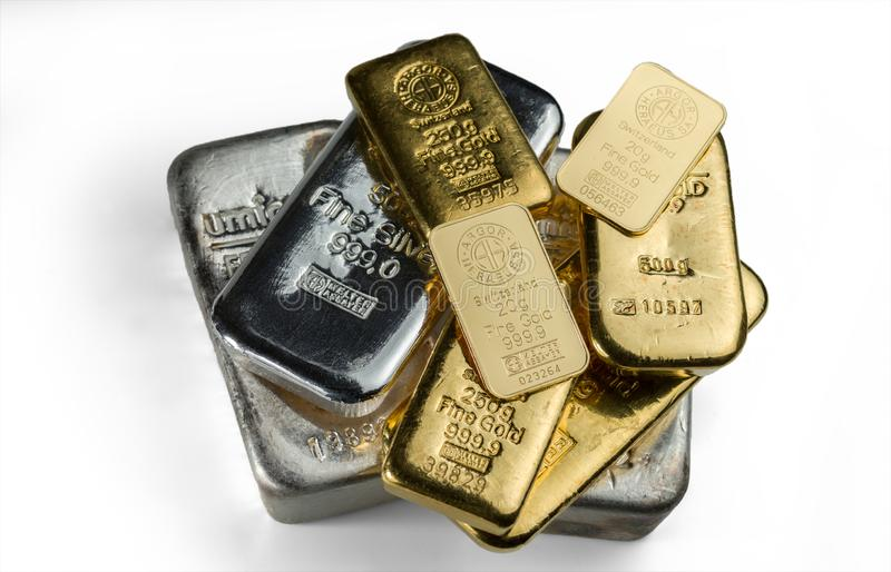 A pile of gold and silver bars from different manufacturers lies on a white background stock photos