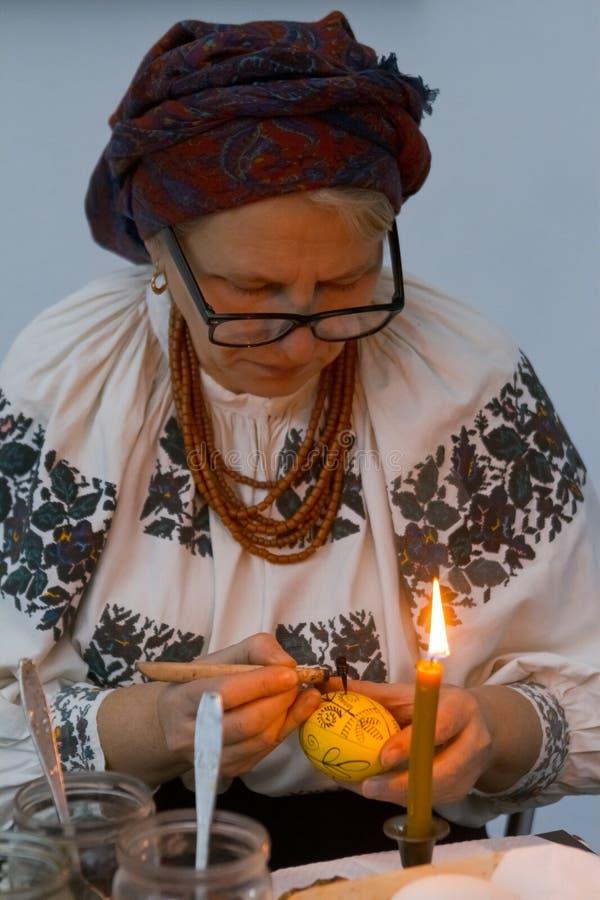 Kyiv, Ukraine - 17.11.2017: experienced woman pysankar paints Easter egg pysanka with folk ornament royalty free stock photography