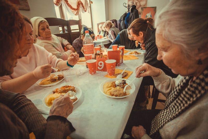 Older poor women having food at the Christmas charity dinner for the homeless. KYIV, UKRAINE - JAN 7: Older poor women having food at the Christmas charity royalty free stock photo