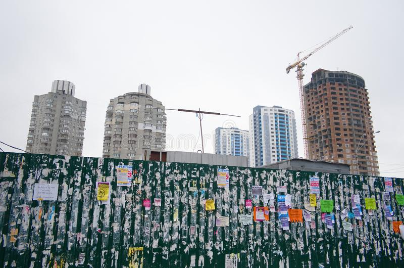 Public bulletin board on the fence on background of construction site of high buildings with cranes stock photo