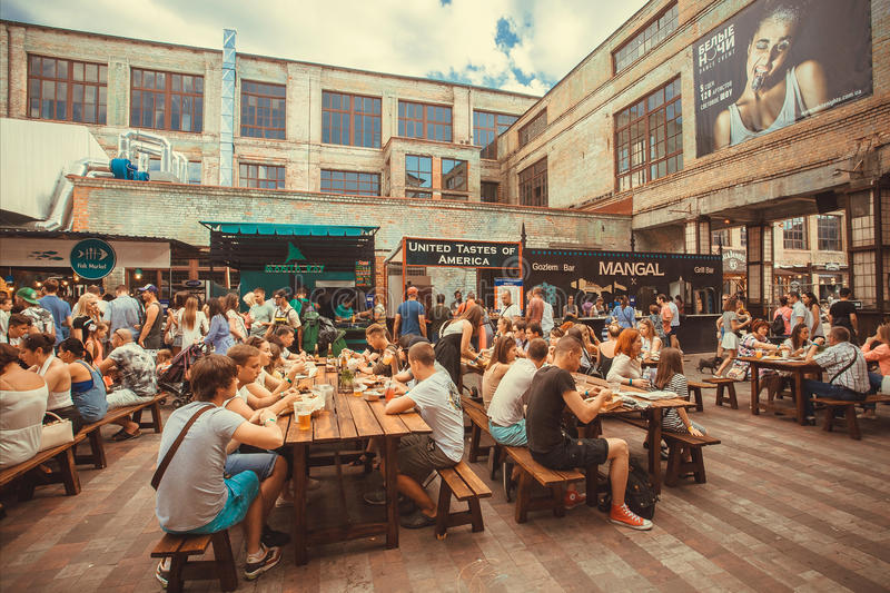 Many tables with friendly party people eating and drinking during outdoor Street Food Festival. KYIV, UKRAINE - JUL 23: Many tables with friendly party people stock photo