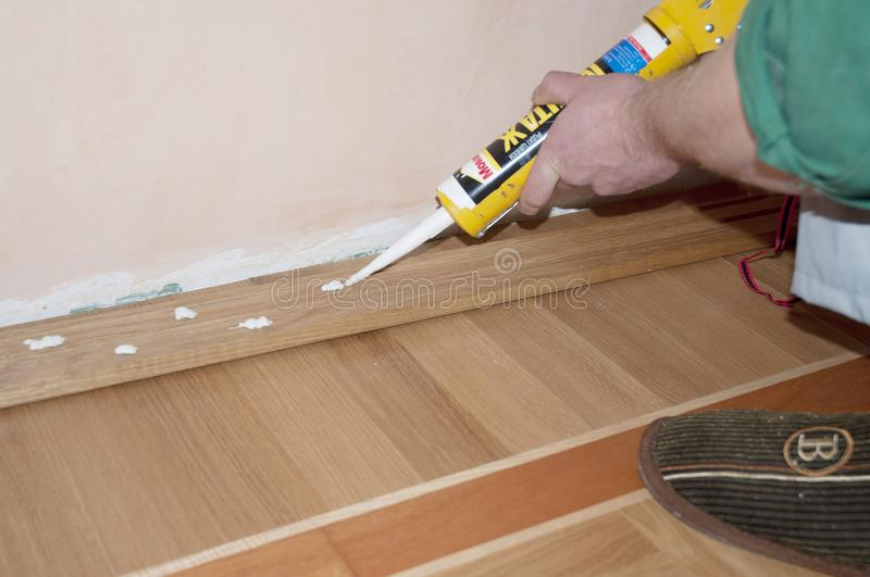 Repairman installing skirting board oak wooden floor with caulking gun silicone from cartridge. Flooring with wooden batten repair royalty free stock image
