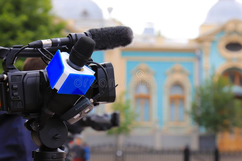 Television journalist with a microphone and a camera at a mass event, press conference. Blue microphone and equipment stock image