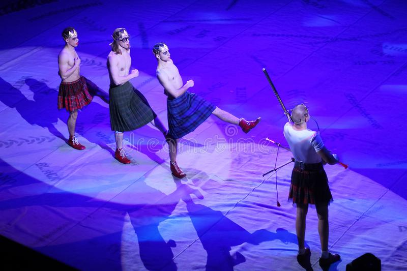 Modern clowns in scottish kilts on circus stage stock images
