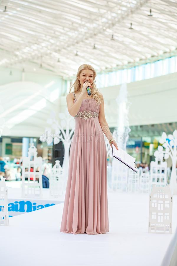 Kyiv, Ukraine March 03.2019. UKFW. Ukrainian Kids Fashion Day. Moderator of the fashion shows with microphone at the podium stock images
