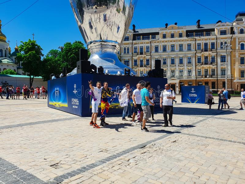 KYIV, UKRAINE - MAY 26, 2018: The final of the Champions League, fans of the real Madrid team stand on the Sofiyskaya square. Near the decorative cup of the royalty free stock photos