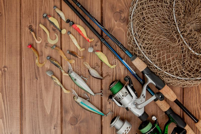 Kyiv, Ukraine- May 15, 2019 Fishing tackle - fishing spinning, hooks and lures on wooden background with copy space.  stock images