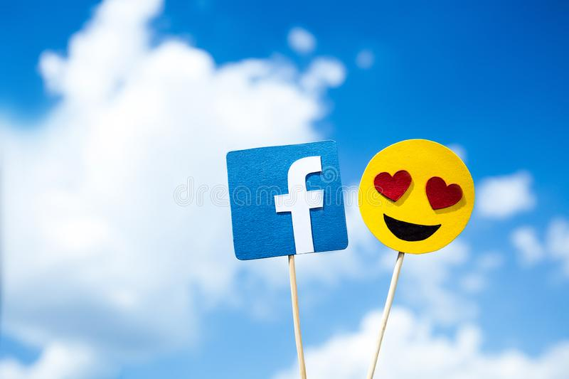 KYIV, UKRAINE - MAY 25, 2019: paper cut Facebook icon and heart eyes emoji. On blue sky background royalty free stock images