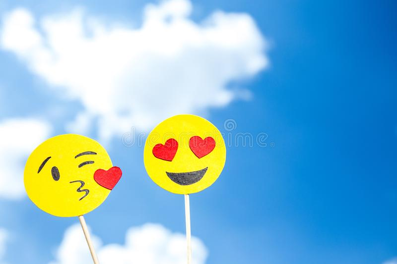 KYIV, UKRAINE - MAY 25, 2019: paper cut heart eyes and blowing kiss emoji. On blue sky background with clouds royalty free stock photo