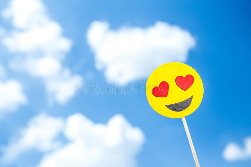KYIV, UKRAINE - MAY 25, 2019: paper cut heart eyes emoji. On blue sky background with clouds royalty free stock images