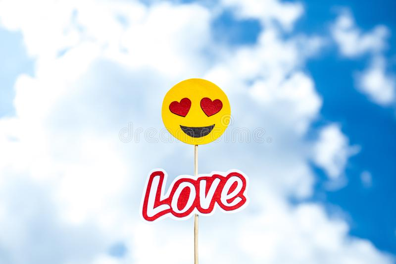 KYIV, UKRAINE - MAY 25, 2019: paper cut heart eyes emoji and love word. On blue sky background with clouds stock images