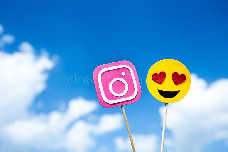 KYIV, UKRAINE - MAY 25, 2019: paper cut Instagram icon and heart eyes emoji. On blue sky background royalty free stock photography