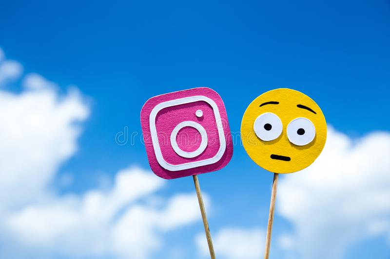 KYIV, UKRAINE - MAY 25, 2019: paper cut Instagram icon and scared emoji. On blue sky background royalty free stock photo