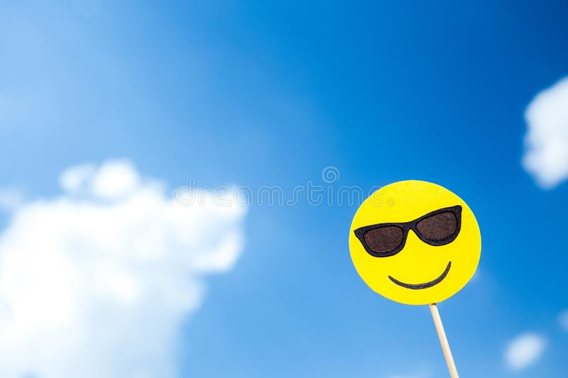 KYIV, UKRAINE - MAY 25, 2019: paper cut smiling face in sunglasses emoji. On blue sky background with clouds stock image
