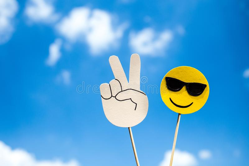 KYIV, UKRAINE - MAY 25, 2019: paper cut victory sign and smiling face in sunglasses. On wooden stick on blue sky background royalty free stock photo