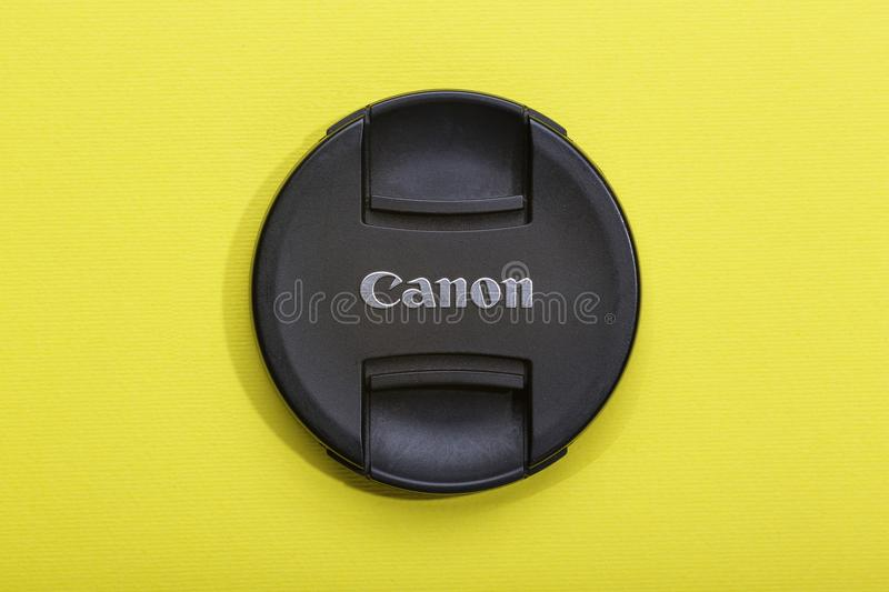 Cap, Canon, Ultrasonic lens, yellow background, top view royalty free stock photography