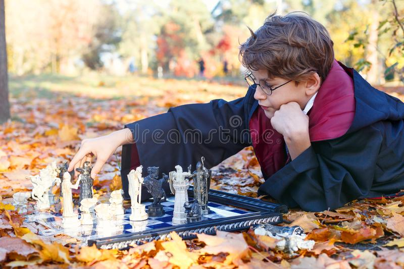 Boy in glasses lies in autumn park with gold leaves, plays chess, makes move, wears in black suit. Kyiv/Ukraine - October 10, 2017: Boy in glasses lies in autumn royalty free stock photos