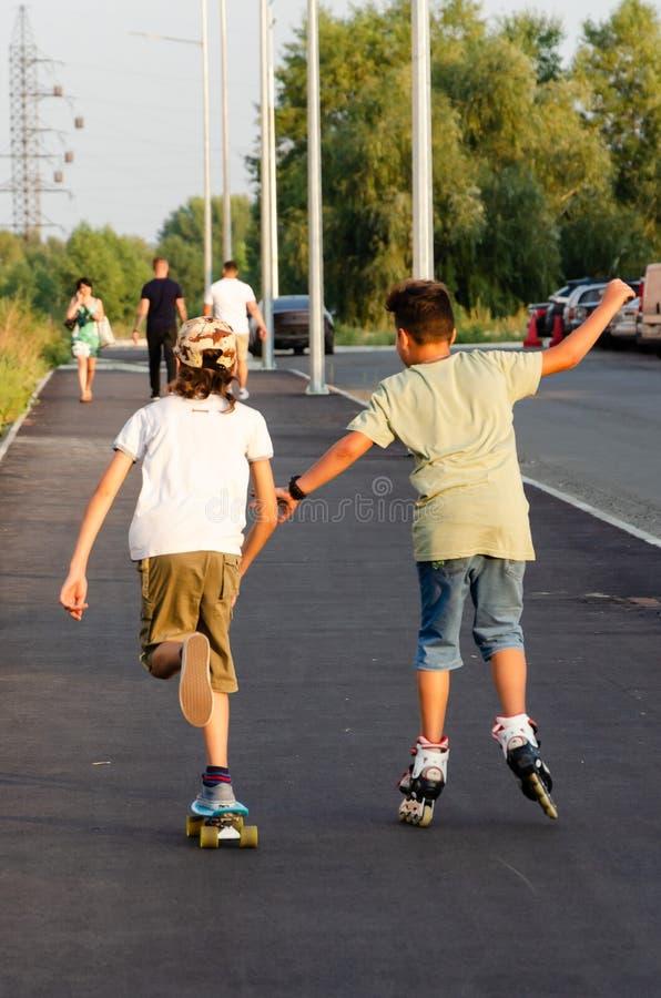 Kyiv, Ukraine - September 01, 2019. Krushelnitskaya St. Two active teens on roller skate and skateboard riding outdoors stock photo