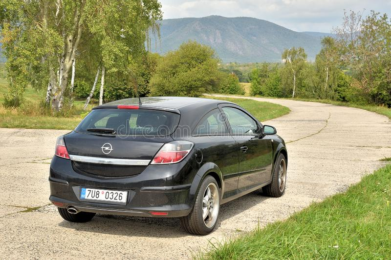 Kyjice, Czech republic - September 08, 2019: black car Opel Astra stand on panel way with Ore mountains on background stock image