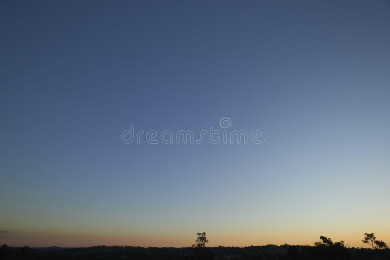 Kyla den blåa solnedgången i öken med trädkonturer royaltyfri foto