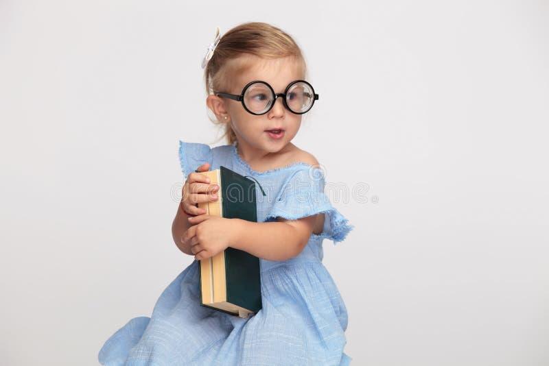 Kyla den nerdy lilla flickan som rymmer hennes bok arkivfoto