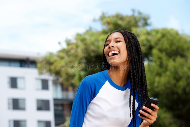 Kyla den svarta flickan som utanför skrattar med mobiltelefonen arkivfoto