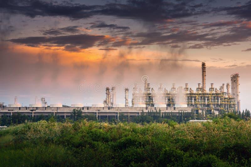 Kyla torn av fossila bränslenraffinaderiväxten på solnedgången Processbyggnader av petrokemisk tillverkning , Affärsteknik och royaltyfri bild