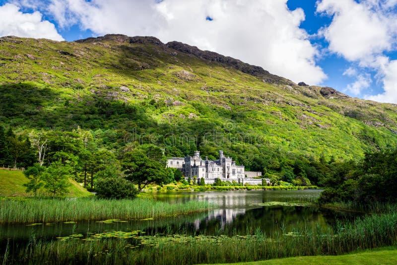 Kylemoreabdij met bezinning in meer bij de voet van een berg Connemara, Ierland stock foto's