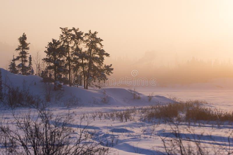 Kylig vintersoluppgång på ram sjön, Yellowknife arkivbilder
