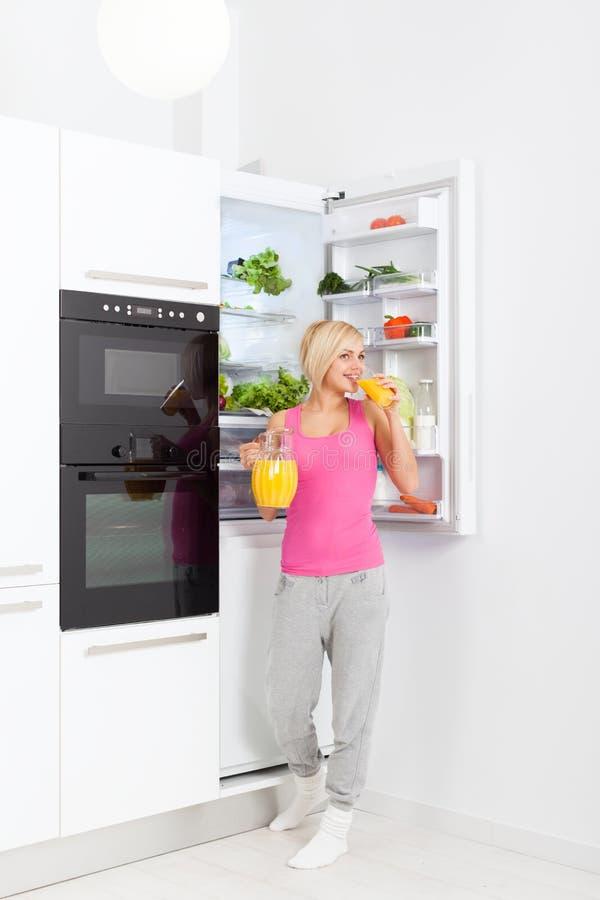 Kylskåp för exponeringsglas för håll för orange fruktsaft för kvinnadrink royaltyfria foton