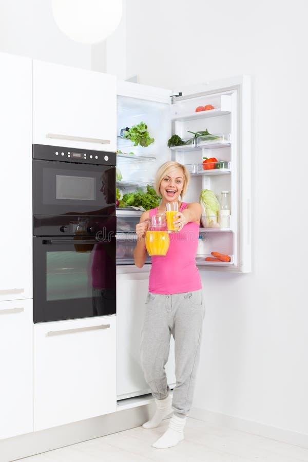 Kylskåp för exponeringsglas för håll för orange fruktsaft för kvinnadrink royaltyfri fotografi