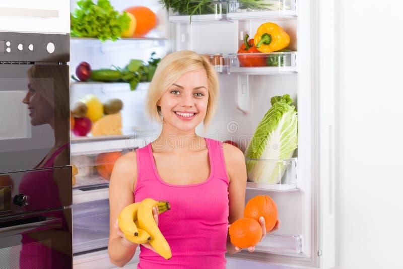 Kylskåp för kvinnabananapelsin arkivfoton