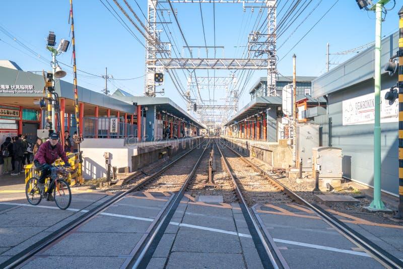 Kyoto, Giappone - 2 marzo 2018: Treno in attesa locale dei turisti e del giapponese attraverso la via sul modo al santuario di Fu fotografia stock libera da diritti