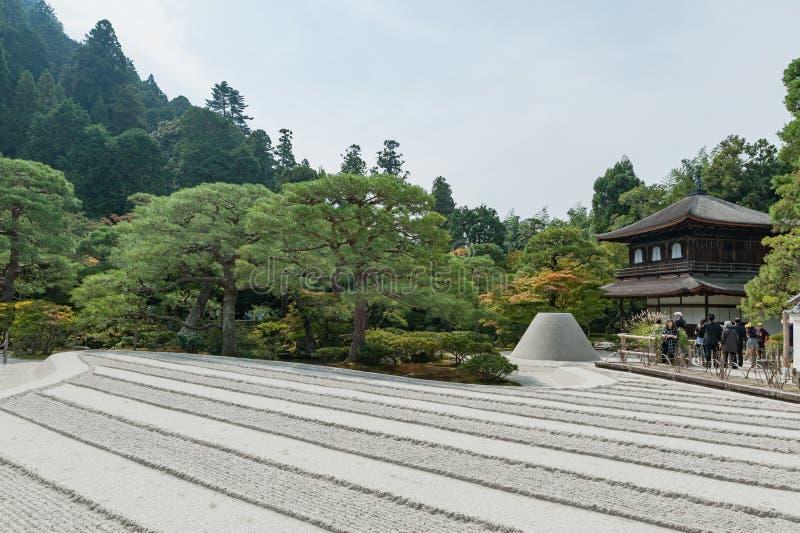 KYOTO, GIAPPONE - 9 OTTOBRE 2015: Santuario e giardino a Kyoto, Giappone Alberi e sabbia verdi Con la gente locale fotografia stock