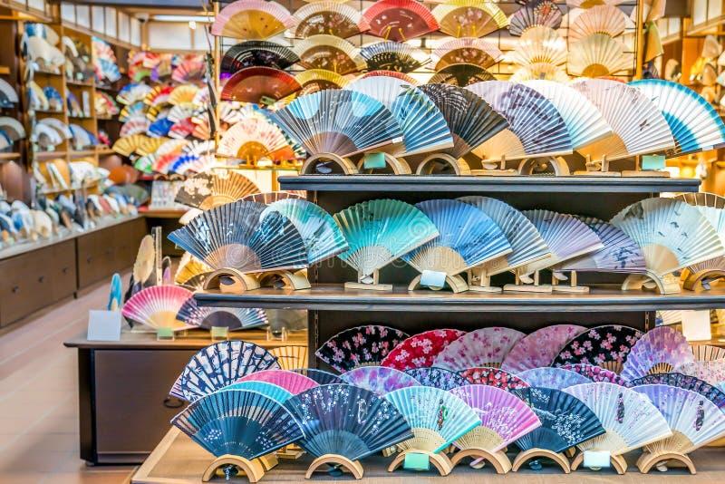 Kyoto, Japão - 2 de março de 2018: O fã de dobramento japonês tradicional é arranjado na prateleira de exposição na frente das lo imagens de stock royalty free