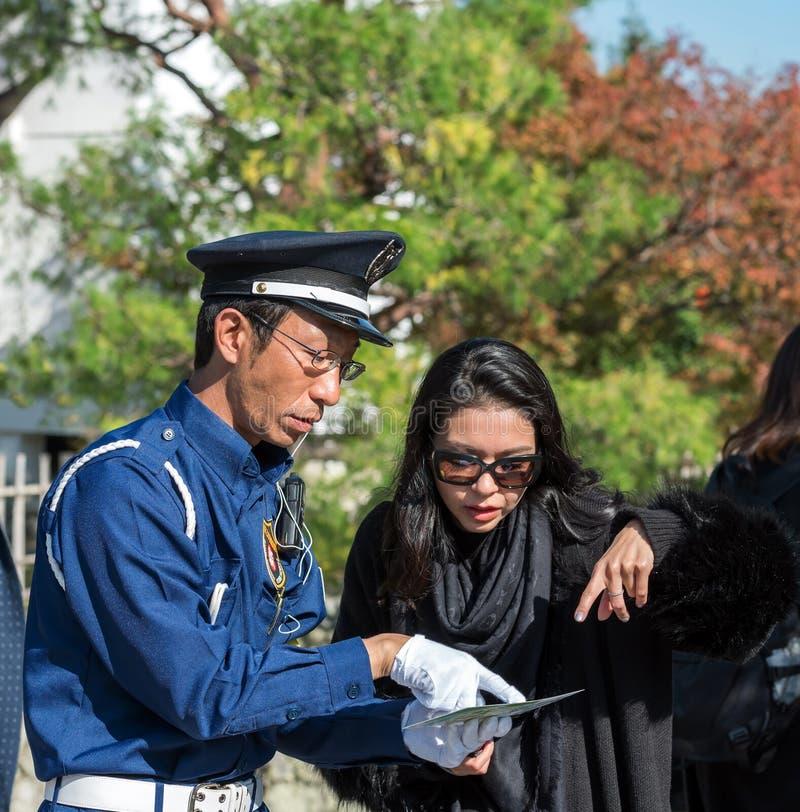 KYOTO, JAPÃO - 7 DE NOVEMBRO DE 2017: Um turista e um polícia em uma rua da cidade imagens de stock royalty free