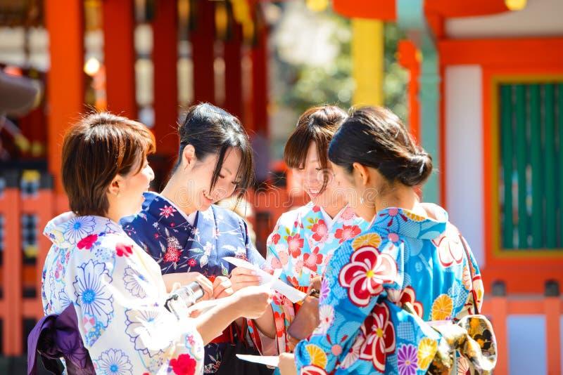 Kyoto, Japón - 28 de marzo de 2015: Mujer japonesa en kimono que lee tiras de la predicción de la fortuna de O-mikuji de papel en foto de archivo libre de regalías