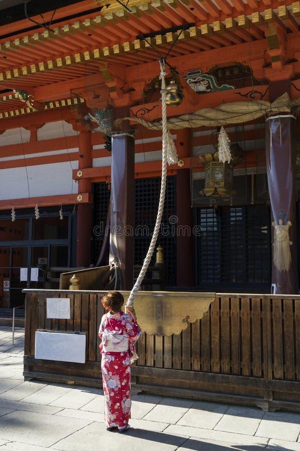 Kyoto, Japón - 18 de mayo de 2017: Mujer en el kimono que tira del campana-ro fotografía de archivo
